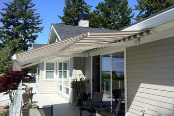 A Royal Marcesa retractable awning provides a cool shady space on a sun-baked deck